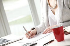Businesswoman fill the form. Businesswoman sitting at desk and fill the form stock photos