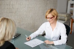 Businesswoman fill out a form in office. Blonde businesswoman fill out a form in office stock photos