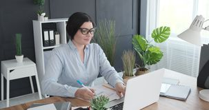 Businesswoman filling form using laptop at office. Businesswoman filling a document using laptop at office desk stock video footage