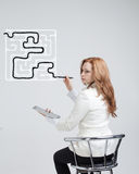 Businesswoman finding the maze solution writing on. Young businesswoman finding the maze solution writing on the whiteboard royalty free stock photo