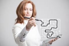 Businesswoman finding the maze solution writing on. Young businesswoman finding the maze solution writing on the whiteboard stock image