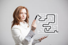 Businesswoman finding the maze solution writing on. Young businesswoman finding the maze solution writing on the whiteboard royalty free stock images
