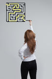 Businesswoman finding the maze solution writing on. Young businesswoman finding the maze solution writing on the whiteboard stock photo