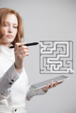 Businesswoman finding the maze solution writing on. Young businesswoman finding the maze solution writing on the whiteboard royalty free stock photos