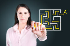 Businesswoman finding the maze solution. Young businesswoman finding the maze solution writing on the whiteboard stock photography