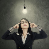 Businesswoman finds solution under lamp Stock Image