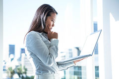 Businesswoman with finger on cheek using laptop Stock Image