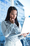 Businesswoman with finger on cheek using laptop Royalty Free Stock Image