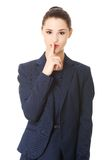 Businesswoman with finger on her lips Stock Photo