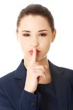Businesswoman with finger on her lips Stock Photography