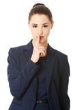 Businesswoman with finger on her lips Royalty Free Stock Photography