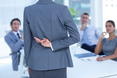 Businesswoman with fingers crossed behind her back. In an office Stock Images