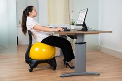 Businesswoman With Fitness Ball And Computer Stock Photo