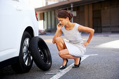 Businesswoman flat tire. Woman calling for assistance with flat tire on car in the city Royalty Free Stock Image