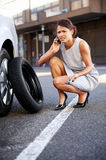 Businesswoman flat tire. Woman calling for assistance with flat tire on car in the city Stock Image