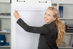 Businesswoman With Flip Chart In Office. Portrait of young businesswoman with flip chart in office stock photography