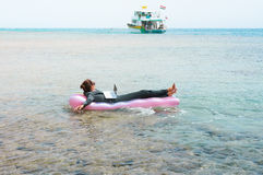 Businesswoman floating on lilo in sea with laptop. Young Caucasian businesswoman wearing suit floating on lilo with laptop and looking at yacht at sea. Female Stock Images