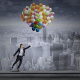 Businesswoman flying with air balloons over the city Stock Photo