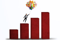 Businesswoman flying with balloons over graph isolated Stock Photos