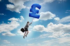 The businesswoman flying on british pound sign inflatable balloon. Businesswoman flying on british pound sign inflatable balloon Stock Photography