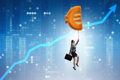 The businesswoman flying on euro sign inflatable balloon. Businesswoman flying on euro sign inflatable balloon Royalty Free Stock Image