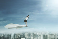 Businesswoman flying with a paper aeroplane Royalty Free Stock Photo