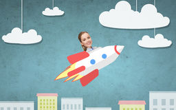 Businesswoman flying on rocket above cartoon city Stock Photos