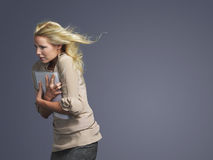Businesswoman With Folder And Blond Hair Blowing In Wind Royalty Free Stock Images