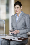 Businesswoman with folder in lap, holding mobile phone, smiling, portrait Stock Photo