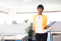 Businesswoman with folder standing in office Stock Photography