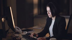 Businesswoman in formal suit is working on computer night shift sitting at desk typing and looking at screen. Busy young. Businesswoman in formal suit is working stock video