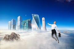 Businesswoman in formal wear flying in blue sky. stock photos