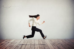 Businesswoman in formal wear running and jumping. Young pretty serious woman in formal wear running and jumping Stock Images