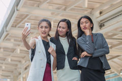 Businesswoman friends selfie with smartphone and pointing at screen surprised Royalty Free Stock Images
