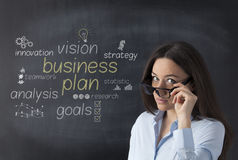 Businesswoman in front of blackboard with business strategy plan Stock Images