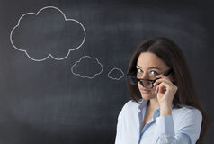 Businesswoman in front of blackboard with thought bubble Royalty Free Stock Photos