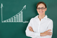 Businesswoman In Front Of Graph Drawn On Chalkboard Royalty Free Stock Photo