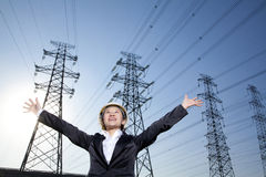 Businesswoman in front of power lines with arms oustretched Stock Images