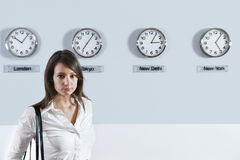 Businesswoman In Front Of World Time Zone Clocks Royalty Free Stock Photography