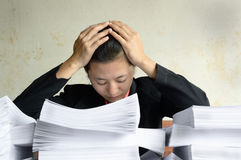 Businesswoman frustrated and helplessly. At a table with a pile of papers Stock Image
