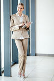 Businesswoman full length. Happy young businesswoman full length portrait with a tablet computer royalty free stock images