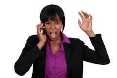 Businesswoman furious over the phone. A black businesswoman furious over the phone Stock Image