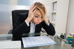 Businesswoman with gantt progress chart at desk Stock Photo
