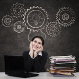 Businesswoman with gear and lightbulb Royalty Free Stock Images