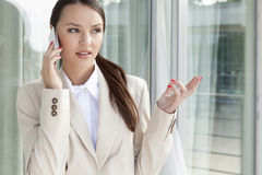 Businesswoman gesturing while answering cell phone against glass door Stock Image