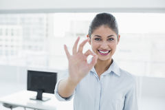 Businesswoman gesturing ok sign in office Stock Photo
