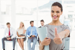 Businesswoman gesturing thumbs up against people waiting for interview Royalty Free Stock Photo
