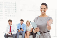 Businesswoman gesturing thumbs up against people waiting for interview Stock Photography