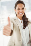 Businesswoman gesturing thumbs up in office Stock Photos