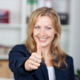 Businesswoman Gesturing Thumbs Up Sign In Office Royalty Free Stock Photography